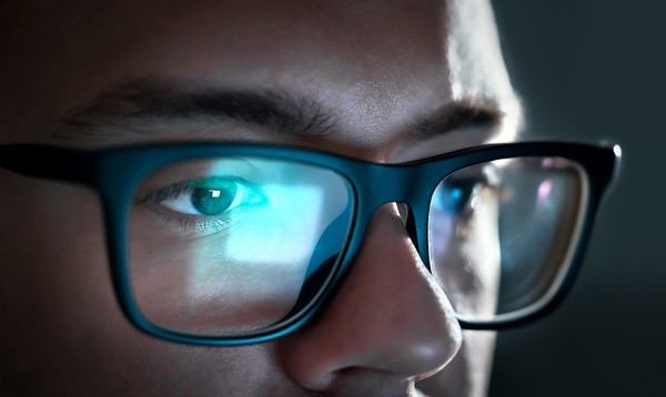 Close up of a man's eyes, a computer screen reflected in his glasses.