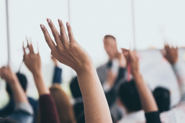 A show of hands at a meeting.